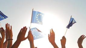 Gente con las manos aumentadas que agitan banderas de la unión europea almacen de video