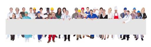 Gente con los diversos empleos que sostienen la cartelera en blanco imágenes de archivo libres de regalías