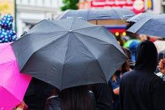 Gente con los paraguas de la lluvia Foto de archivo