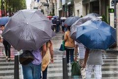 Gente con los paraguas de la lluvia en la ciudad lluviosa Foto de archivo libre de regalías