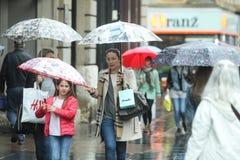 Gente con los paraguas en la calle Fotos de archivo libres de regalías