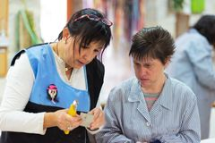 Gente con necesidades o el funcionamiento especiales de la incapacidad con sus profesores en el taller de la terapia profesional imagenes de archivo