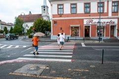 Gente corrente sul passaggio pedonale in pioggia Fotografia Stock