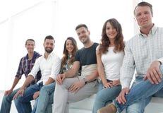 Gente creativa joven que se sienta en sillas en sala de espera Fotos de archivo