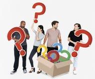 Gente curiosa con los signos de interrogación imagenes de archivo
