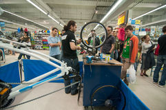 Gente d'istruzione del meccanico come allineare una ruota della bici su un supporto d'allineamento Immagine Stock