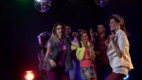 Gente de baile con alegría de la diversión en la discoteca de adolescencias Fume el fondo metrajes
