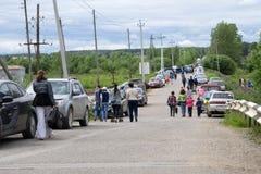 Gente de crisol que cruza la calle antes de puesta del sol Parque y una calle de doble sentido al norte del parque Rusia Usolye 1 imagen de archivo
