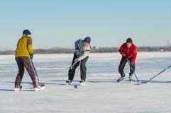 Gente de diversas edades que juegan a hockey en un río congelado Dnepr en Ucrania Foto de archivo