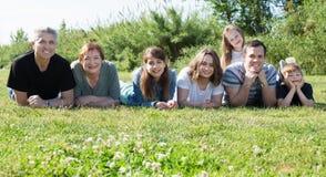 Gente de diversas edades que toman las fotos en el césped Foto de archivo
