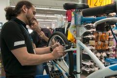 Gente de enseñanza del mecánico cómo ajustar los frenos en una bicicleta Imágenes de archivo libres de regalías