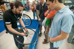 Gente de enseñanza del mecánico cómo instale un casete en un eje de ruedas Imagen de archivo