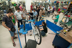 Gente de enseñanza del mecánico cómo reparar una bicicleta Imagen de archivo libre de regalías