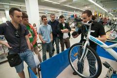 Gente de enseñanza del mecánico cómo reparar una bicicleta Fotos de archivo libres de regalías