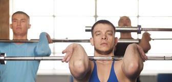 Gente de j?venes en el entrenamiento del gimnasio con los Barbells imagen de archivo