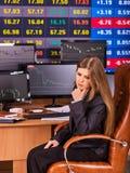Gente de la bolsa de acción Tabla que se sienta de la mujer del comerciante rodeada por los monitores Imagen de archivo libre de regalías