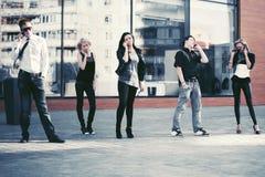 Gente de la moda de los jóvenes que habla en los teléfonos celulares en calle de la ciudad Foto de archivo libre de regalías
