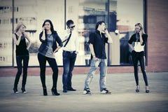 Gente de la moda de los jóvenes que habla en los teléfonos celulares en calle de la ciudad Imagen de archivo