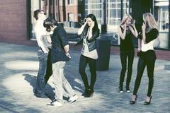 Gente de la moda de los jóvenes que habla en los teléfonos celulares en calle de la ciudad Fotografía de archivo