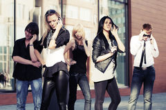 Gente de la moda de los jóvenes que invita a los teléfonos celulares en una calle Imagen de archivo