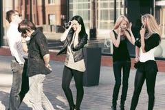 Gente de la moda de los jóvenes que invita a los teléfonos móviles Imagen de archivo libre de regalías