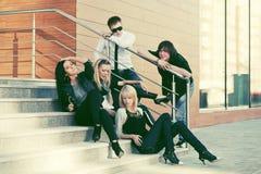Gente de la moda de los jóvenes que se sienta en los pasos en calle de la ciudad Foto de archivo libre de regalías
