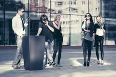 Gente de la moda de los jóvenes que habla en los teléfonos celulares en calle de la ciudad Fotos de archivo