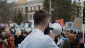 Gente de la reunión en ciudad El individuo grita en el altavoz La muchedumbre en la calle metrajes
