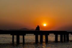 Gente de la silueta con el puente en la puesta del sol Fotos de archivo libres de regalías