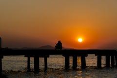 Gente de la silueta con el puente en la puesta del sol Fotos de archivo