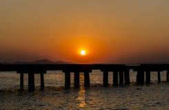 Gente de la silueta con el puente en la puesta del sol Fotografía de archivo