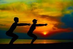 Gente de la yoga que entrena y que medita en actitud del guerrero afuera por la playa en la salida del sol o la puesta del sol Imagen de archivo libre de regalías