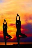 Gente de la yoga que entrena y que medita en actitud del guerrero afuera por la playa en la salida del sol o la puesta del sol Foto de archivo libre de regalías