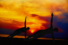 Gente de la yoga que entrena y que medita en actitud del guerrero afuera por la playa en la salida del sol o la puesta del sol Fotos de archivo
