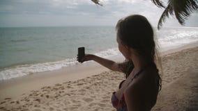 Gente de las vacaciones de la playa - el bañador blanco de la mujer hace el selfie que se relaja mirando el mar perfecto del asiá metrajes