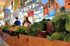 Gente de las ventas detrás de contadores en la cópula del mercado del granjero, PA, 2013. Imagen de archivo