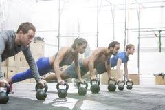 Gente dedicada que hace flexiones de brazos con los kettlebells en el gimnasio del crossfit Foto de archivo libre de regalías