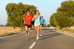Gente del deporte que corre en camino Foto de archivo libre de regalías