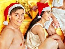 Gente del grupo en el sombrero de Papá Noel en la sauna. Foto de archivo