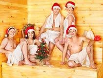 Gente del grupo en el sombrero de Santa en la sauna. Imagenes de archivo