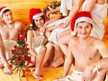 Gente del grupo en el sombrero de Santa en la sauna. Fotografía de archivo