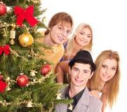 Gente del grupo por el árbol de navidad. Imagenes de archivo