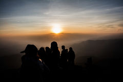 Gente del grupo que mira la puesta del sol Imagenes de archivo