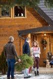 Gente del grupo que prepara la casa de la montaña para la Nochebuena imagen de archivo libre de regalías