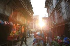 Gente del Nepali que camina abajo de la calle de Thamel bajo salida del sol por la mañana en Katmandu Foto de archivo libre de regalías