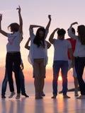 Gente del partido en puesta del sol imagen de archivo