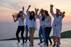 Gente del partido en puesta del sol foto de archivo