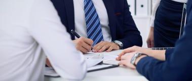 Gente di affari ad una riunione nell'ufficio Metta a fuoco sull'uomo del capo mentre firmano il contratto o le carte finanziarie fotografia stock