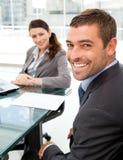 Gente di affari allegra che si siede ad una tabella Fotografia Stock