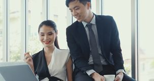 Gente di affari asiatica che utilizza computer portatile nell'ufficio video d archivio